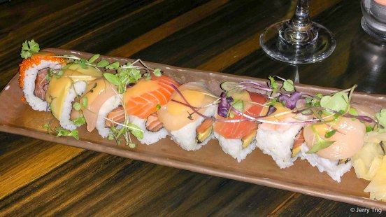 Rainbow roll, inside out roll with salmon and avocado topped with chef's selection of sashimi and yuzu lemonade