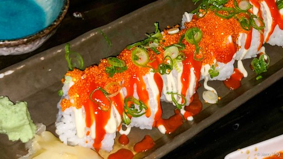 Dragon roll, inside out roll with seared tuna, cucumber, avocado, tobiko, Japanese mayo, chilli sauce, spring onion